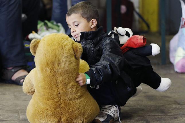 Niños juegan con peluches que les regalan en la entrada de Munich.